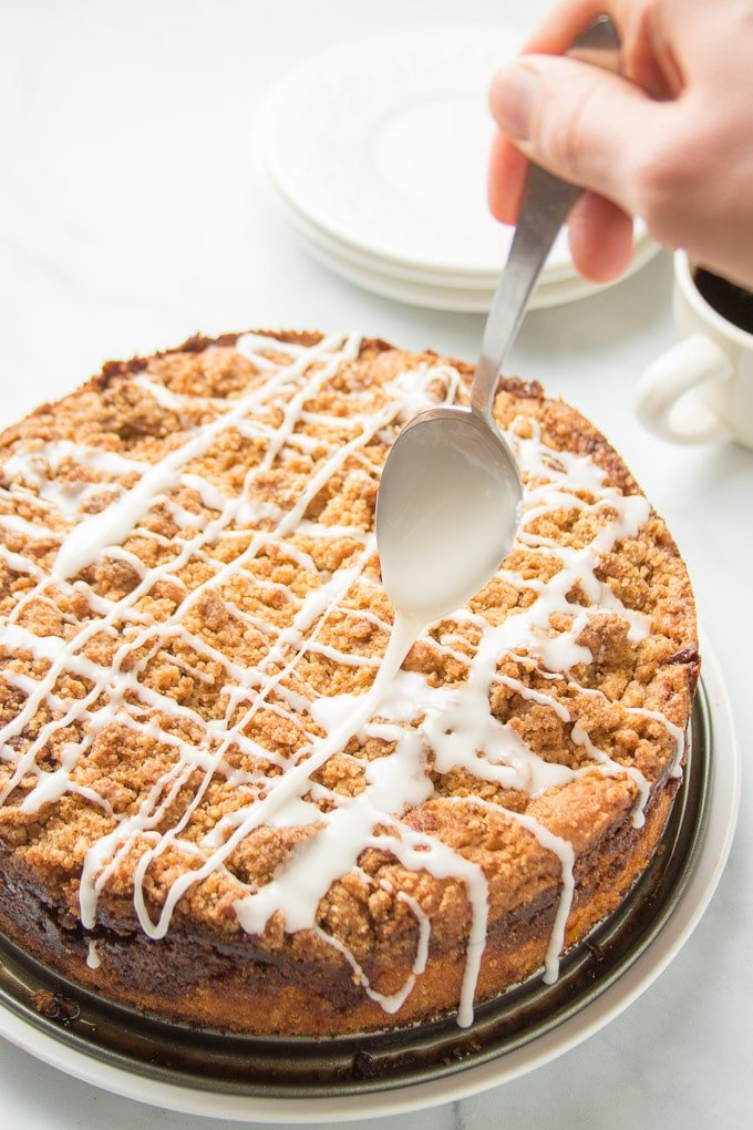 Spoon Drizzling Glaze on a Vegan Coffee Cake