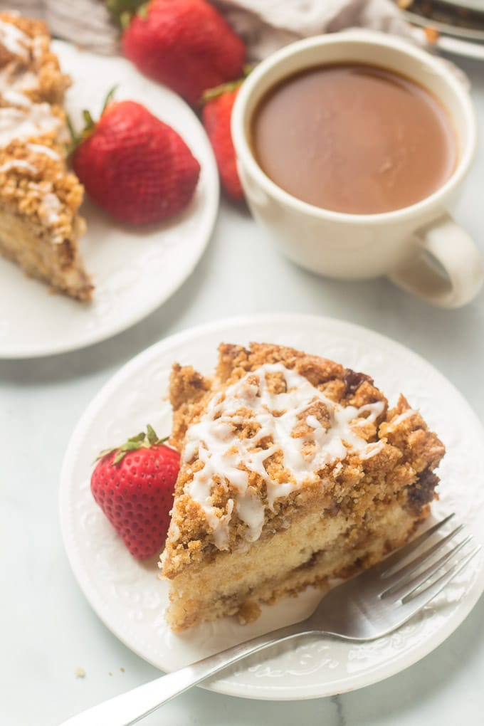 Two Slices of Vegan Coffee Cake on a Table with Coffee and Strawberries