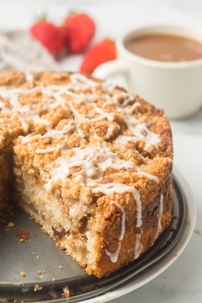 Partially Sliced Vegan Coffee Cake with Coffee Cup in the Background