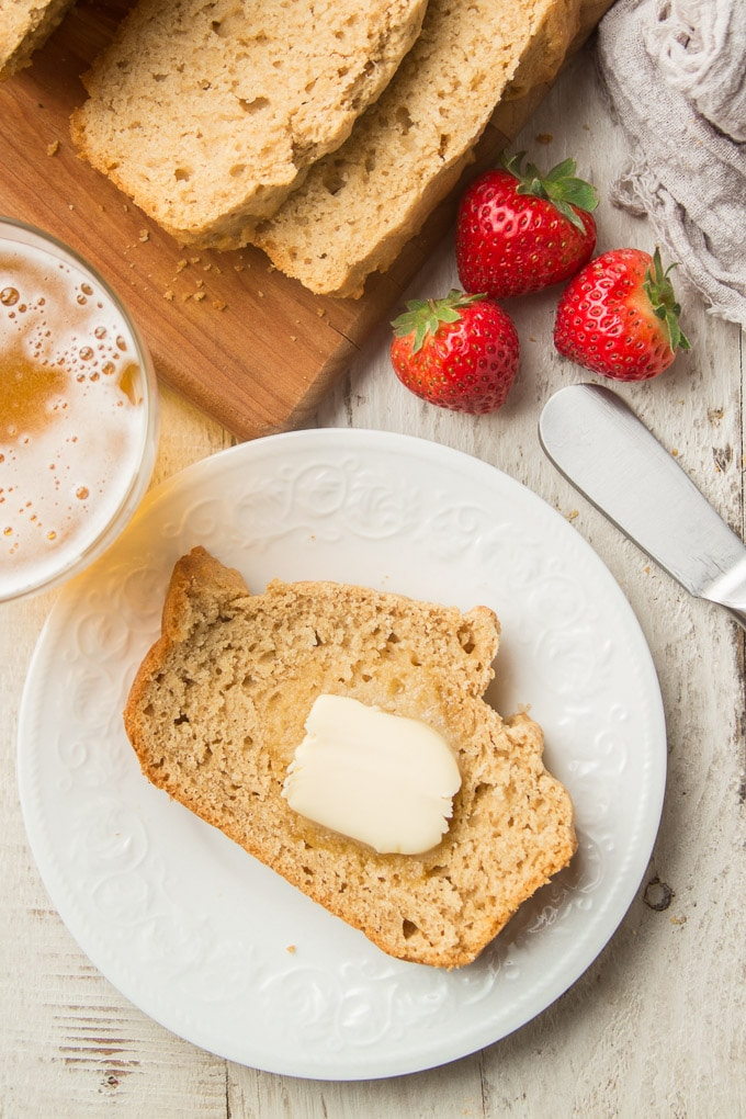 White Wooden Surface Set with Slices of Beer Bread on a Cutting Board, Slice of Beer Bread on a Plate, Glass of Beer, and Three Strawberries