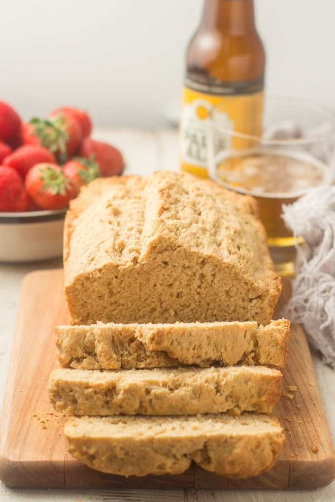 Loaf of Beer Bread with Glass and Bottle of Beer, and Bowl of Strawberries in the Background