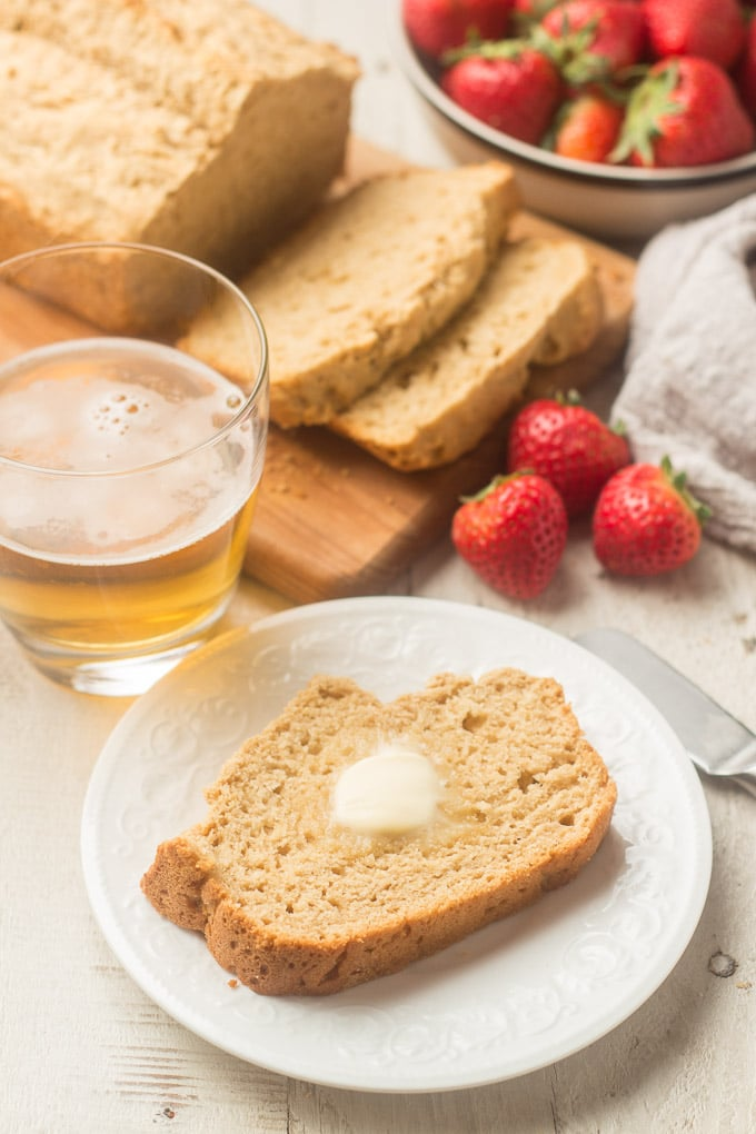 Slice of Whole Wheat Beer Bread, Glass of Beer, and Strawberries on a White Wooden Surface