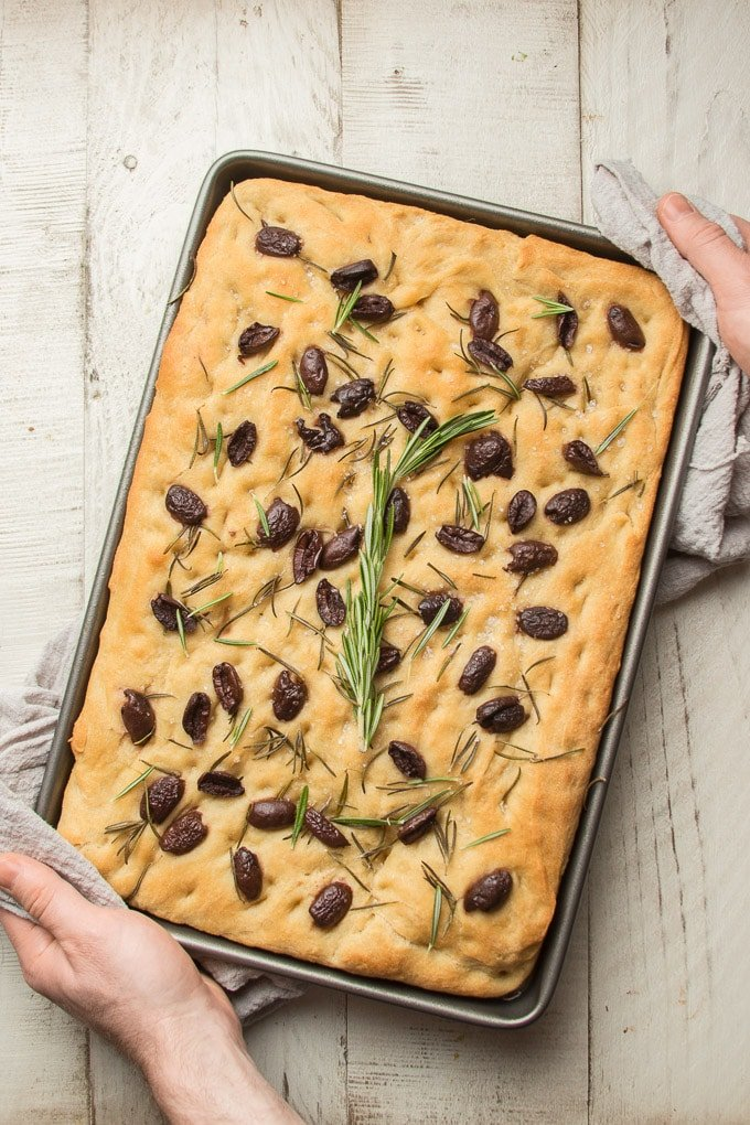 Pair of Hands Holding a Baking Sheet of Olive Rosemary Focaccia Over a Table