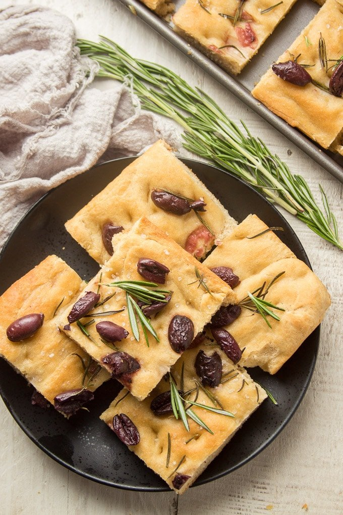 Table Set with a Plate of Olive Rosemary Focaccia, Baking Sheet, and Sprig of Rosemary