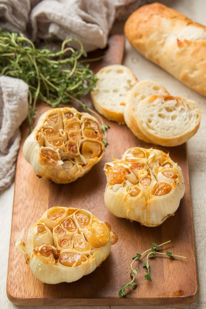 Three Roasted Garlic Bulbs with Thyme and Baguette Slices in the Background