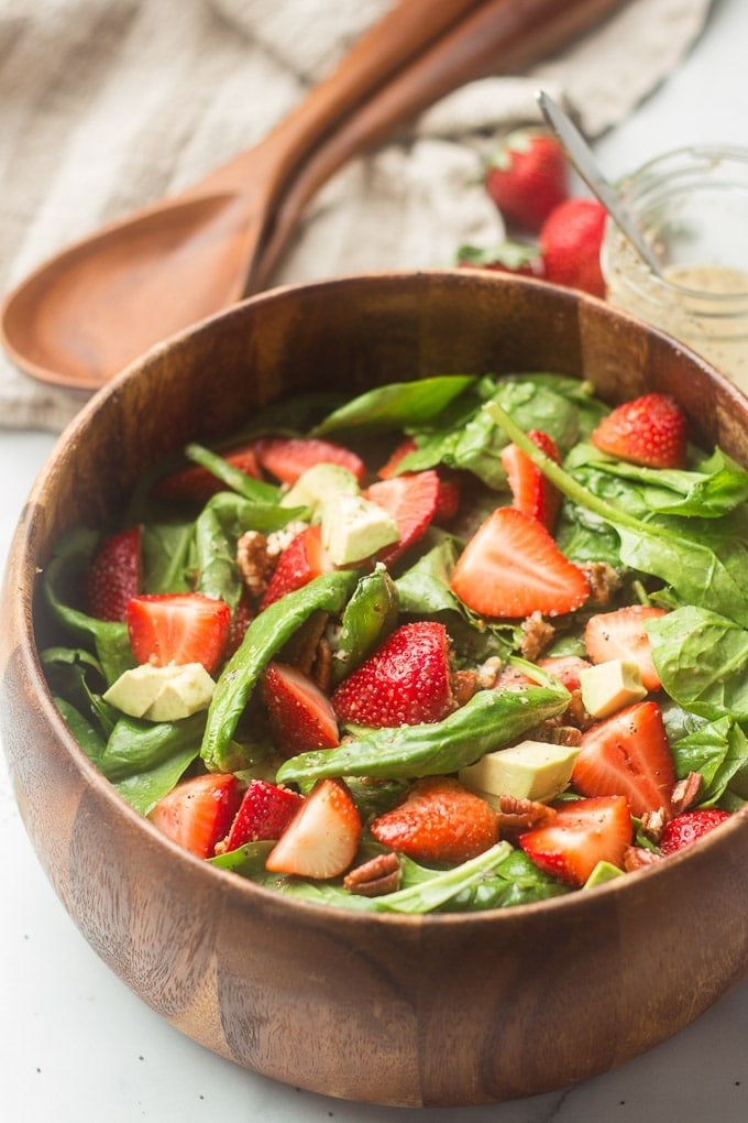Bowl of Strawberry Spinach Salad with Berries and Serving Spoons in the Background