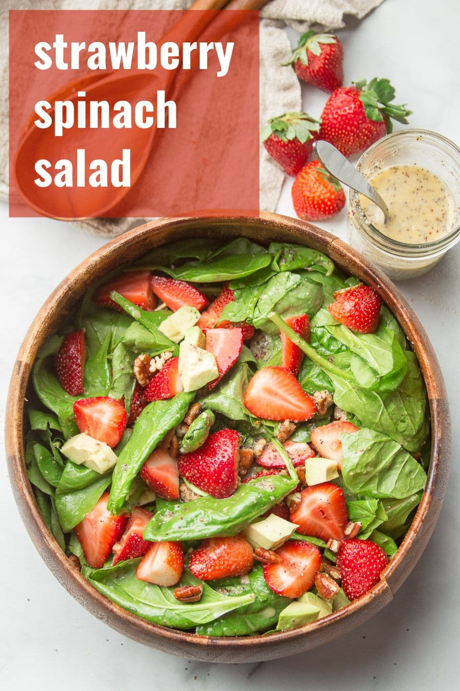 Kitchen Counter Set with a Bowl of Strawberry Spinach Salad, Dressing, Strawberries and Wooden Spoons
