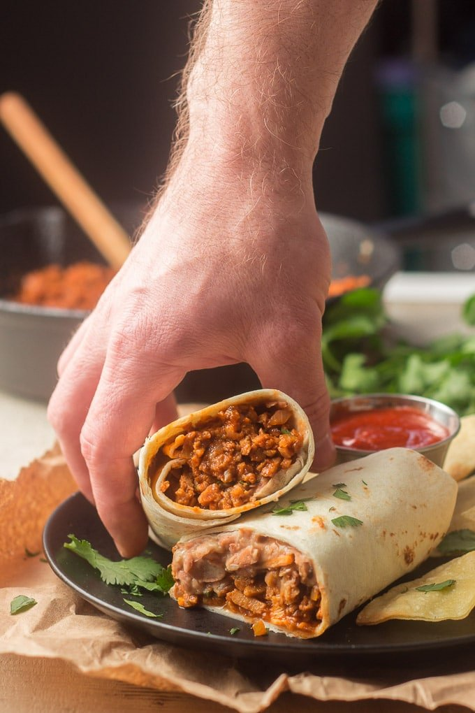 """Hand Grabbing Half of a """"Beefy"""" Vegan Burrito from a Plate"""