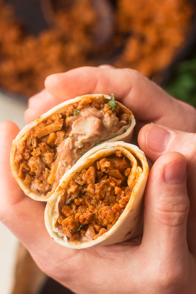 """Pair of Hands Holding Two Halves of a """"Beefy"""" Vegan Burrito"""
