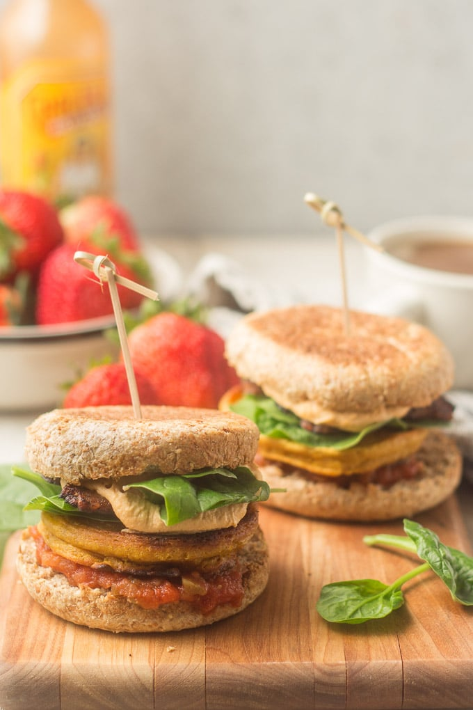 Counter Set with Two Vegan Breakfast Sandwiches on a Cutting Board, Bowl of Strawberries, Coffee Cup and Bottle of Hot Sauce