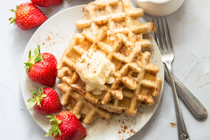 Three Vegan Waffles on a Plate with Strawberries and Butter