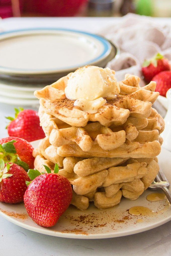 Stack of Five Vegan Waffles with Plates and Strawberries in the Background