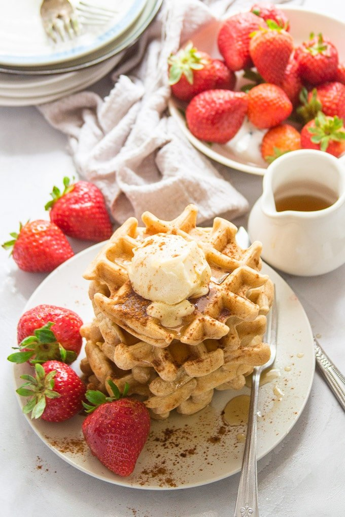Stack of Vegan Waffles on a Plate with Strawberries and Maple Syrup Container in the Background