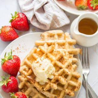 Table Set with a Plate of Vegan Waffles, Bowl of Strawberries, and Container of Maple Syrup