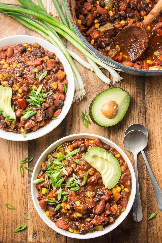Wooden Table Set with Two Bowls of Vegan Chili, Spoons, Drinking Glass and Half an Avocado