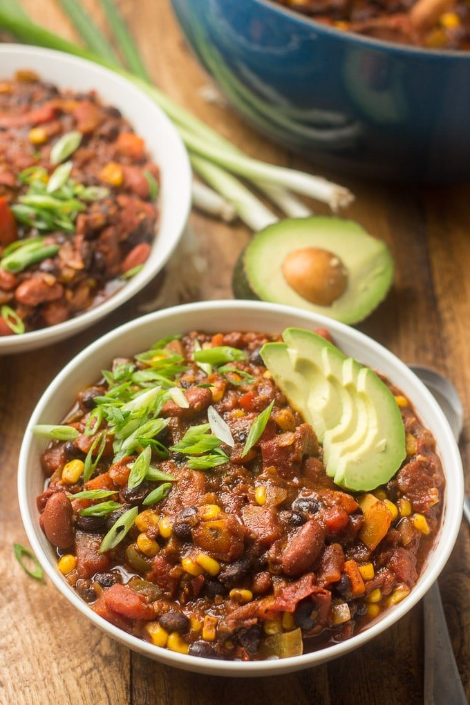 Bowls of Vegan Chili Topped with Avocado with a Blue Pot in the Background