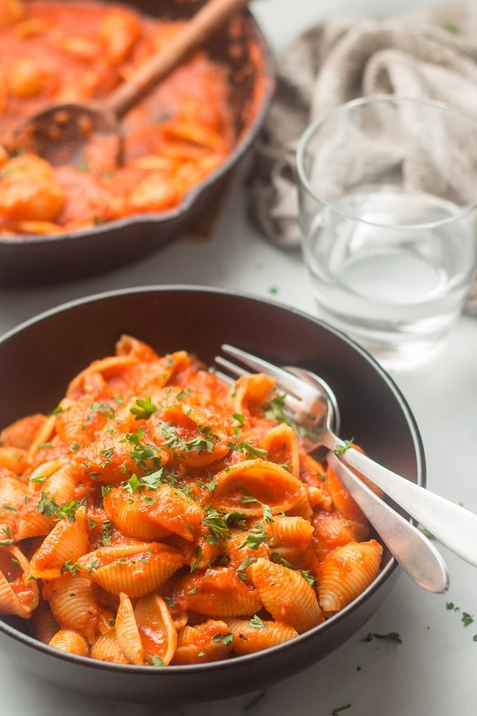 Bowl of Red Pepper Pasta with Skillet and Water Glass in the Background