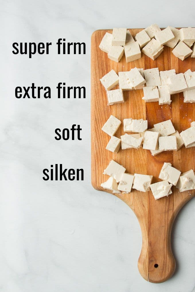 """Cutting Board with 4 Varieties of Diced Tofu with Labels Reading """"Super Firm,"""" """"Extra Firm,"""" """"Soft,"""" and """"Silken"""""""
