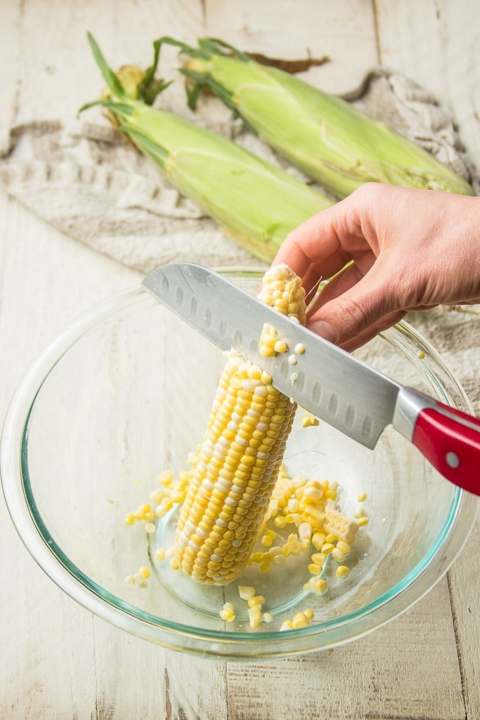 Hand with Knife Cutting Corn off of a Cob Into a Glass Bowl