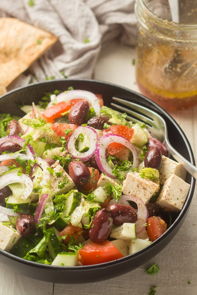 Bowl of Vegan Greek Salad with Pita Bread and Dressing Jar in the Background