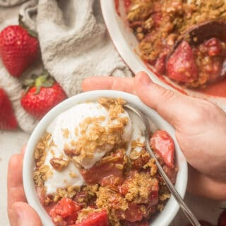 Pair of Hands Holding a Bowl of Vegan Strawberry Crisp and Vanilla Ice Cream Over a Table