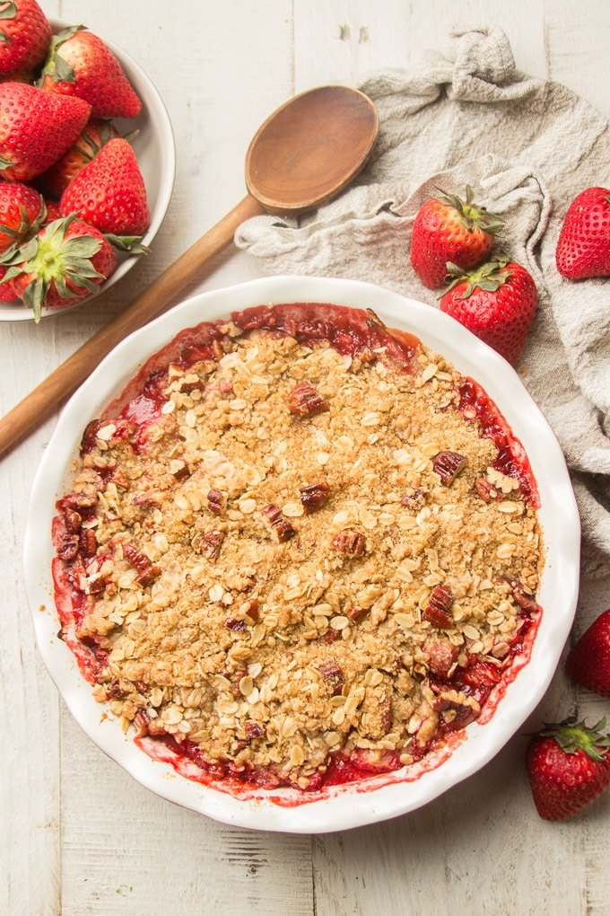 Vegan Strawberry Crisp in a Pie Plate Surrounded By Strawberries, Napkin and Wooden Spoon