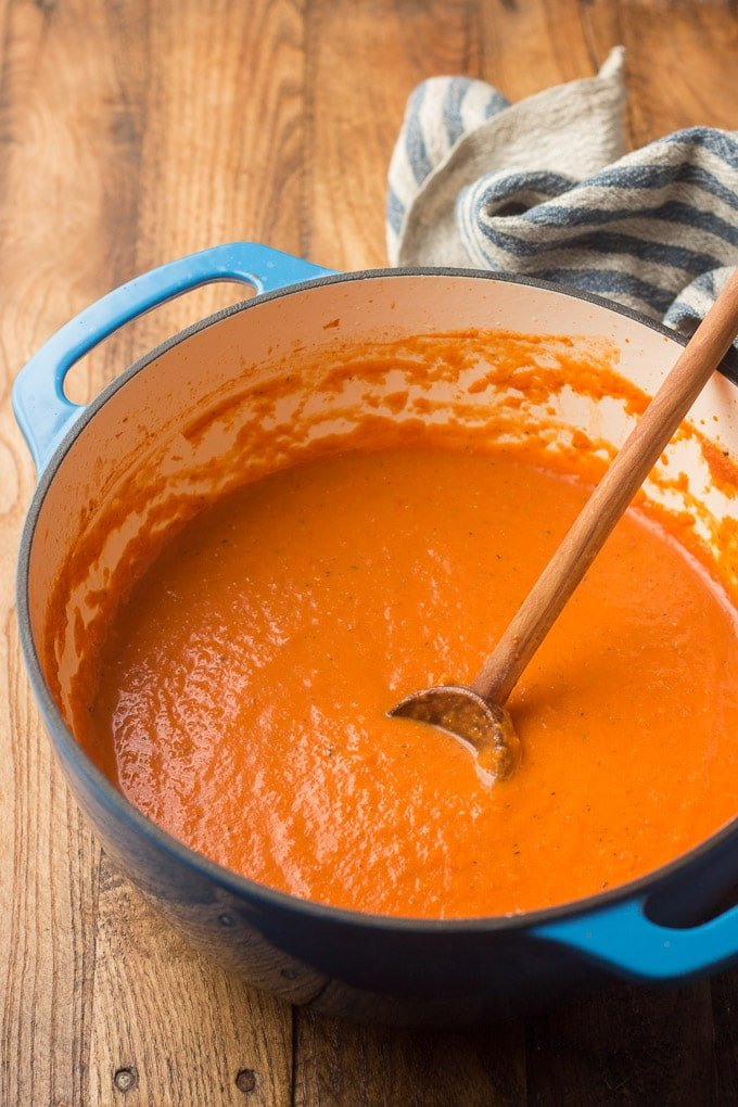 Vegan Tomato Bisque in a Blue Pot with Wooden Spoon