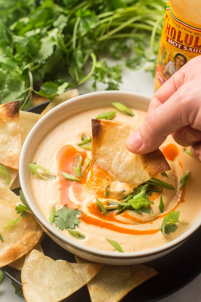 Hand Dipping a Chip in a Bowl of Cashew Queso