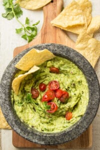 Guacamole Topped with Tomatoes and Cilantro in a Molcajete