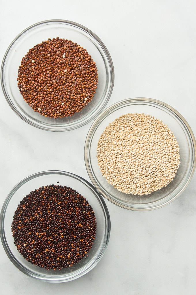 Three Bowls Containing Red, White, and Black Quinoa on a Marble Surface