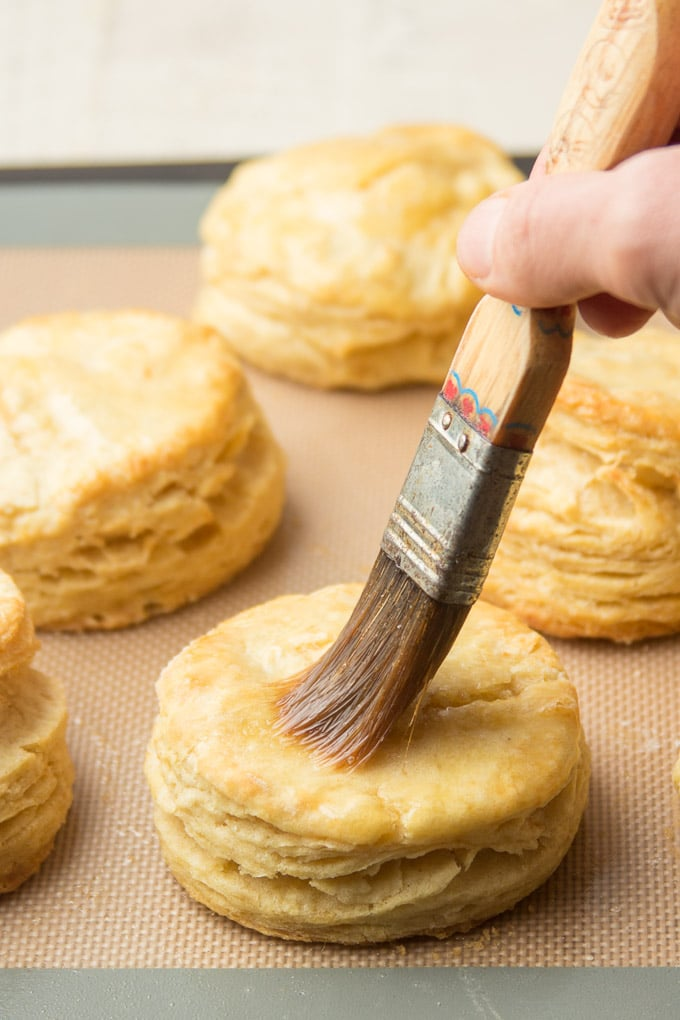 Hand Brusing Melted Vegan Butter on a Biscuit