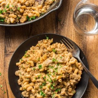 Wooden Table Set with Skillet, Water Glass, and Plate of Vegan Hamburger Helper