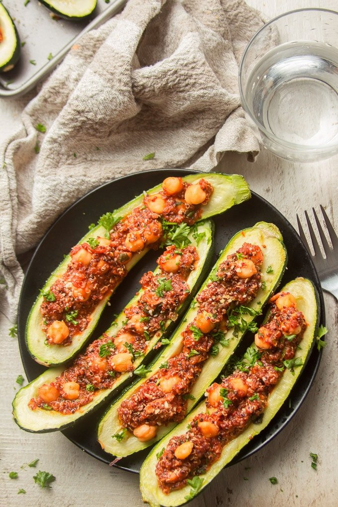 Four Vegan Stuffed Zucchini Halves on a Plate with Napkin and Fork