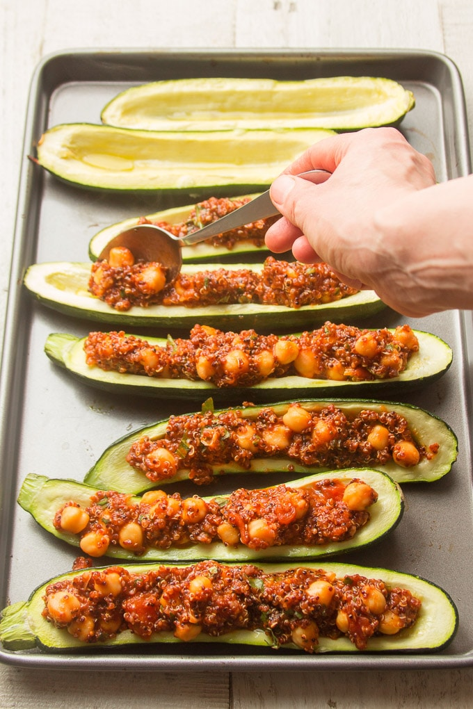 Hand Spooning Filling into Zucchini Halves