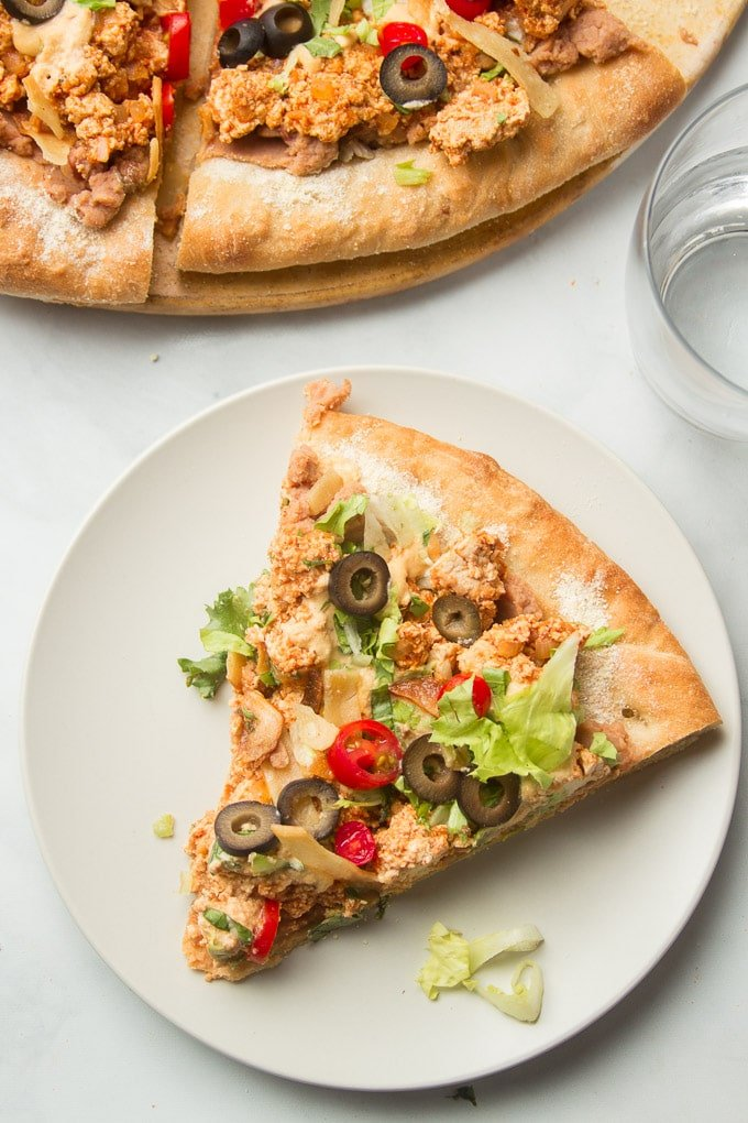 Slice of Vegan Taco Pizza on a Plate on a Marble Background with Water Glass