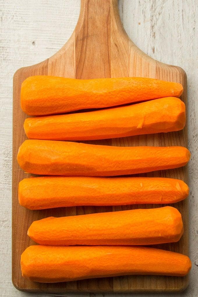 Six Peeled Carrots on a Cutting Board