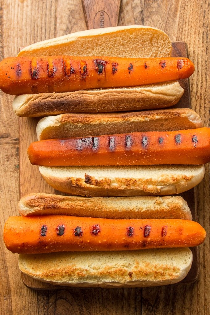 Three Carrot Dogs Without Toppings on a Wooden Surface