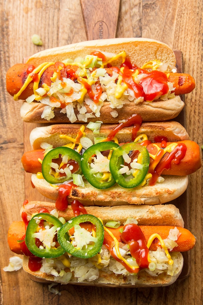 Three Carrot Dogs Topped with Ketchup, Mustard, Sauerkraut and Jalapeno Slices on a Wooden Surface