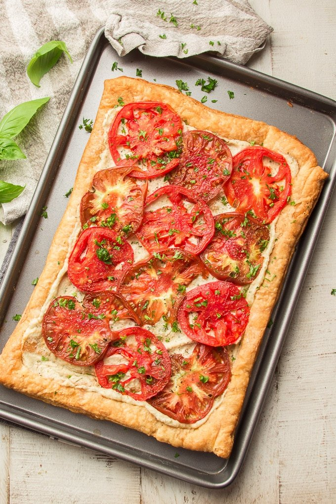 Tomato Tart on a Baking Sheet, Napkin, and Basil Leaves Arranged on a White Wooden Surface