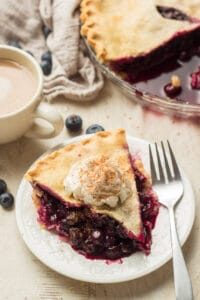 Slice of Vegan Blueberry Pie on a Plate with Coffee Cup, Napkin, and Rest of Pie in the Background