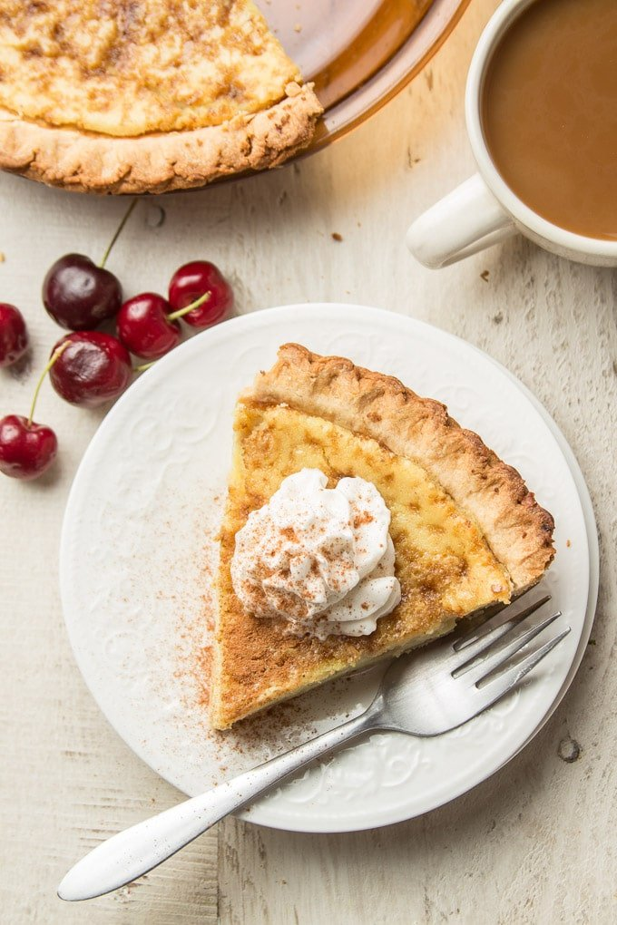 Slice of Vegan Custard Pie with Whipped Topping on a Plate Surrounded by Coffee Cup and Cherries