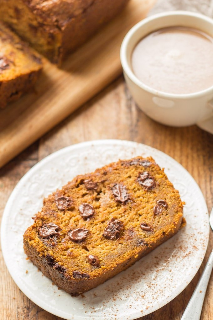Slice of Vegan Pumpkin Bread on a Plate with Coffee Cup in the Background