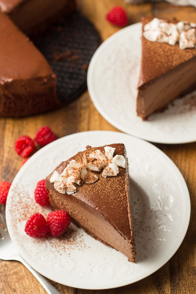 Wooden Surface Set with Vegan Chocolate Cheesecake and Two Slices on Plates with Raspberries