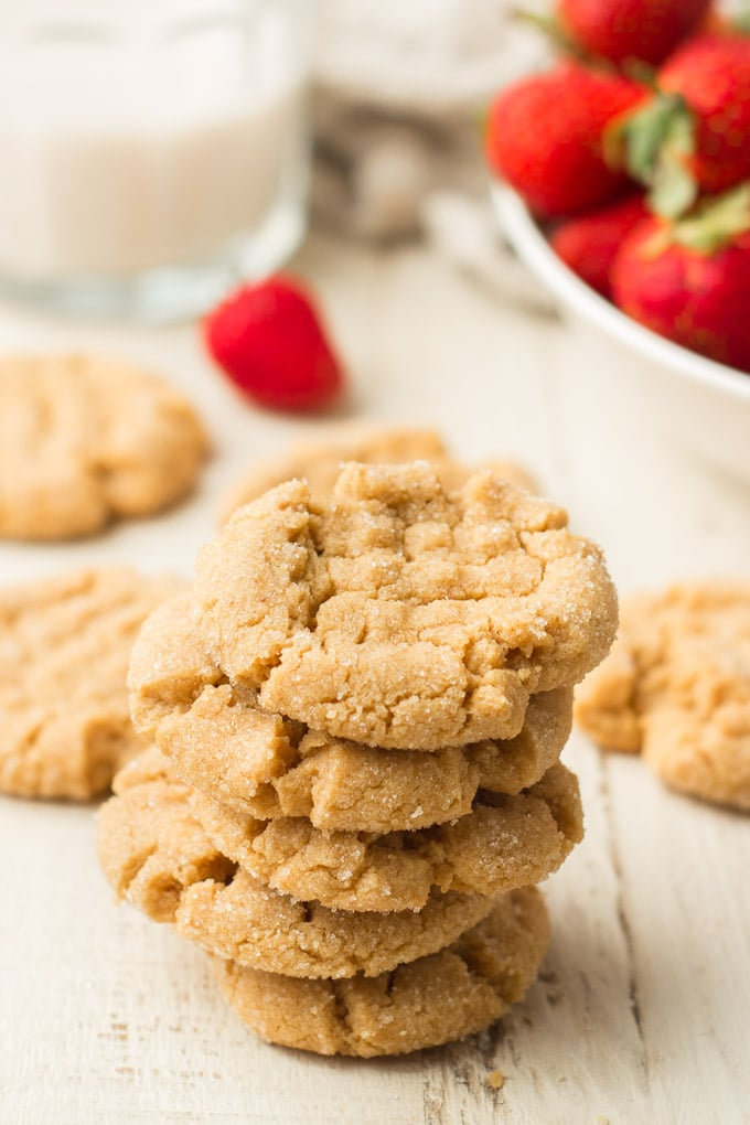 Stack of Vegan Peanut Butter Cookies on a White Wooden Surface with Glass of Almond Milk and Bowl of Strawberries