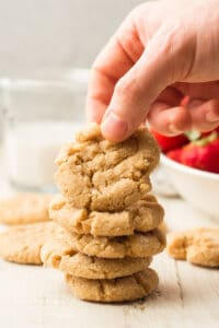 Hand Grabbing a Vegan Peanut Butter Cookie From a Stack