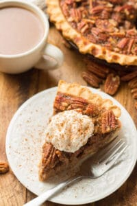 Slice of Vegan Pecan Pie with Whipped Topping on a Plate, with Coffee Cup and Rest of Pie in Background