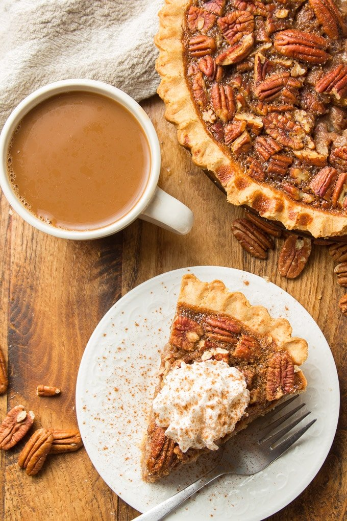 Overhead View of a Wooden Table Set with Vegan Pecan Pie, Coffee Cup, and Slice of Pie on Plate