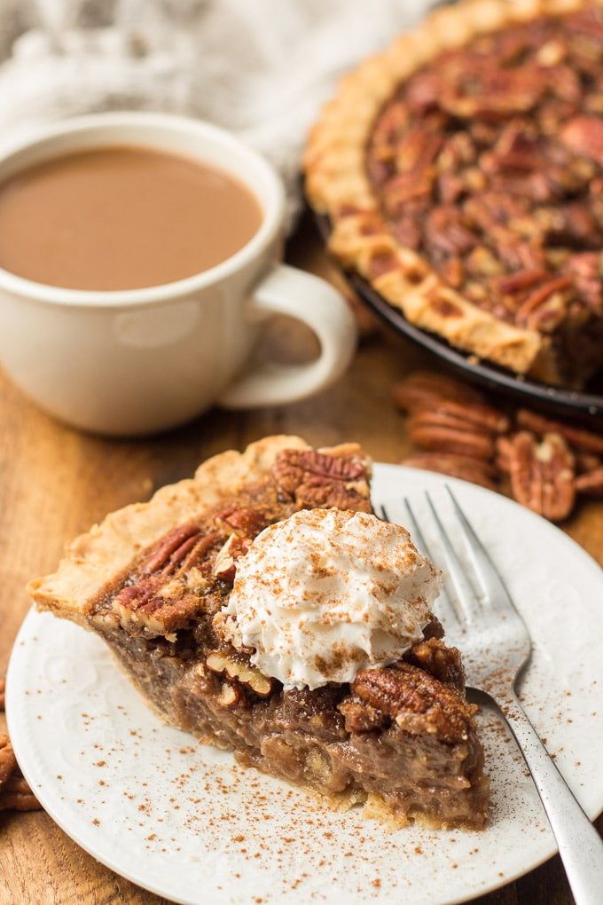 Slice of Vegan Pecan Pie on a Plate with Fork, with Pecans, Coffee Cup and Pie in the Background
