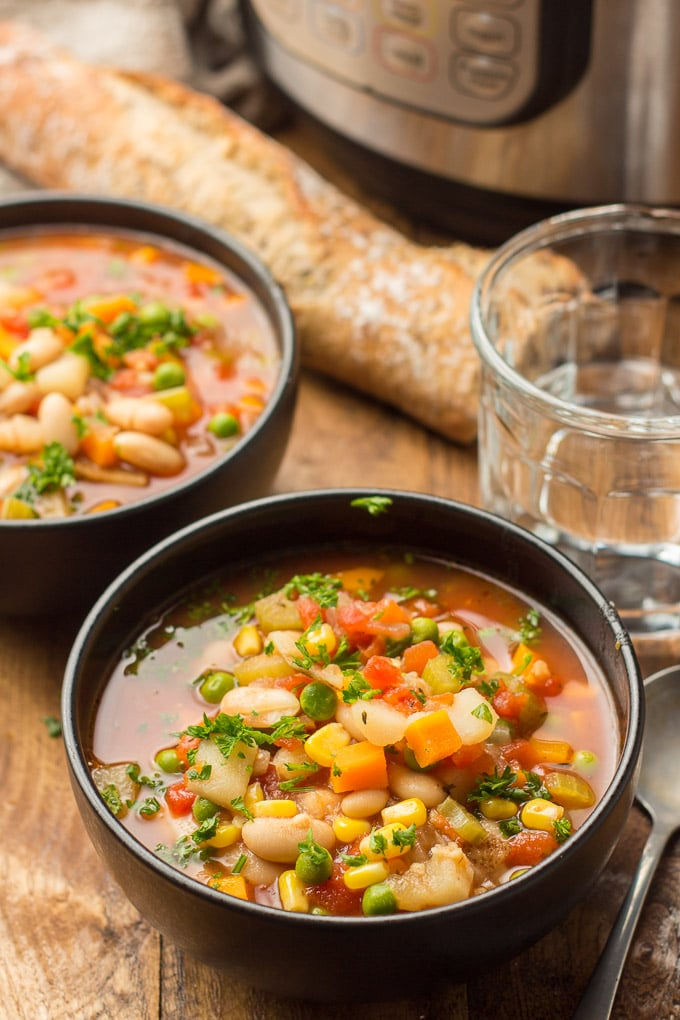 Two Bowls of Instant Pot Vegetable Soup with Water Glass, Baguette, and Instant Pot in the Background