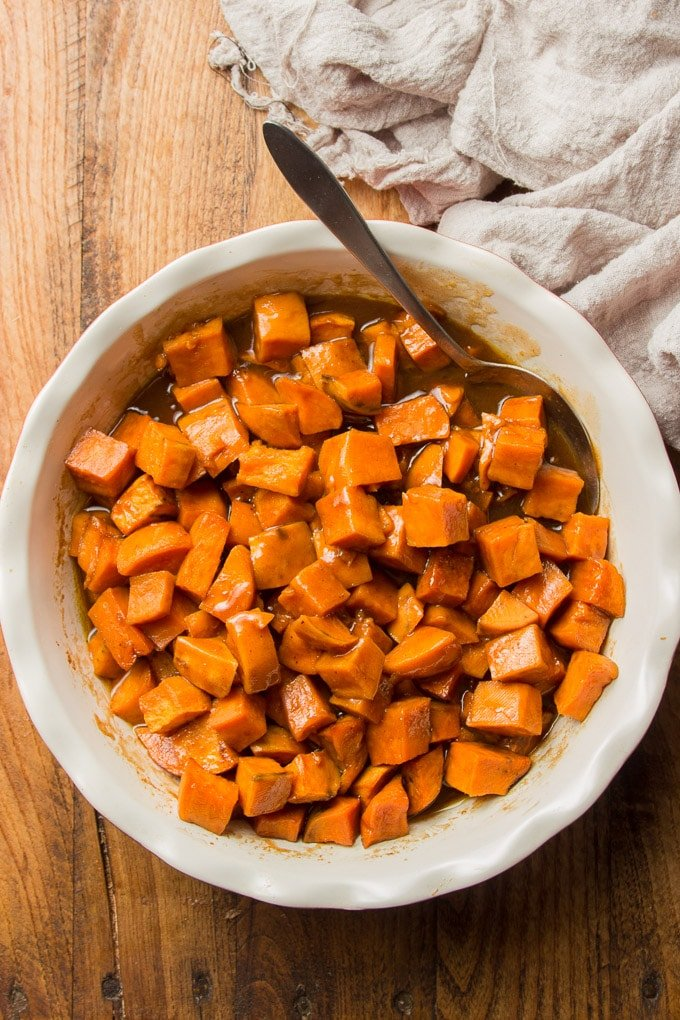 Dish of Vegan Candied Yams and Serving Spoon on a Wooden Surface